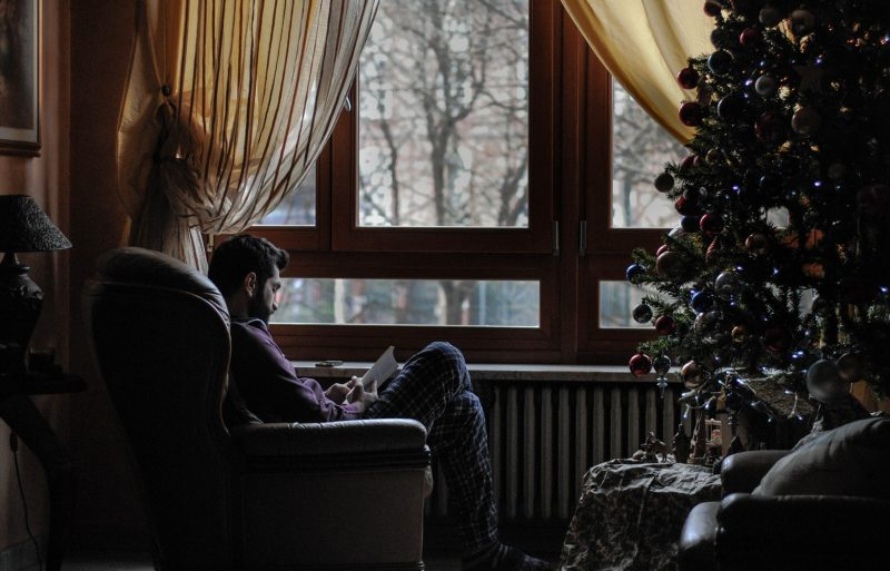 Photo of man sat in leather armchair at Christmas struggling with festive stress reading a book next to a Christmas tree