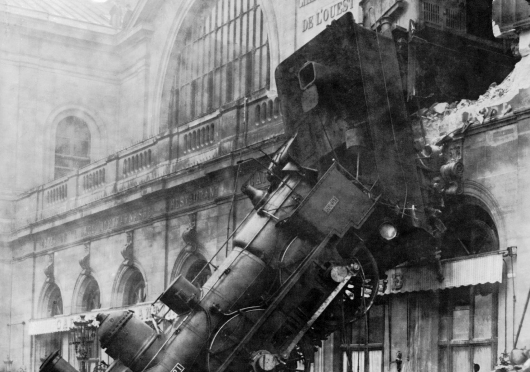 Black and white image of steam train crashed through building because it's the worst that could happen