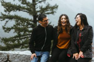 Photo of one man and two women sat on a stone wall laughing and talking about happiness self esteem