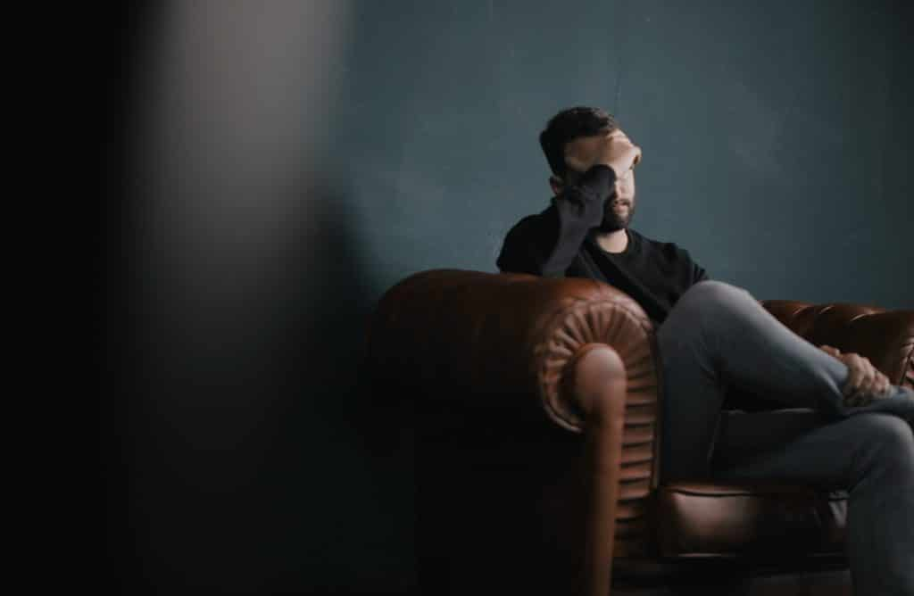 Photo of burden bearded man sat on a leather sofa with hand on head suffering from anxiety depression stress panic attack