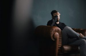 Photo of bearded man sat on a leather sofa with hand on head suffering from anxiety depression stress panic attack