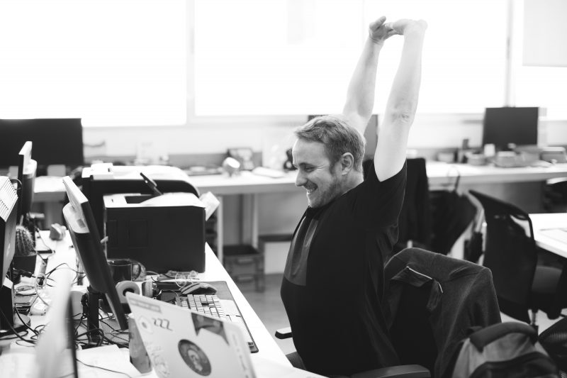 Black and white photo of man working at office desk stretching because he is suffering from business stress and overworked